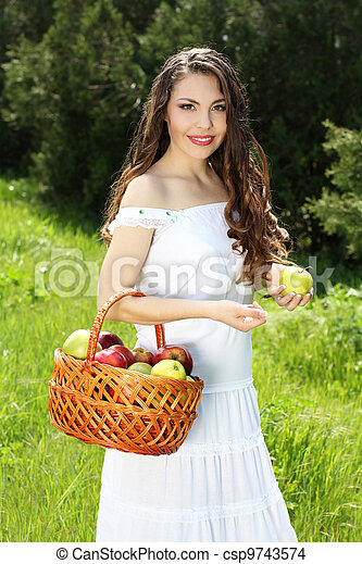 Smiling Female presents basket of apples over nature