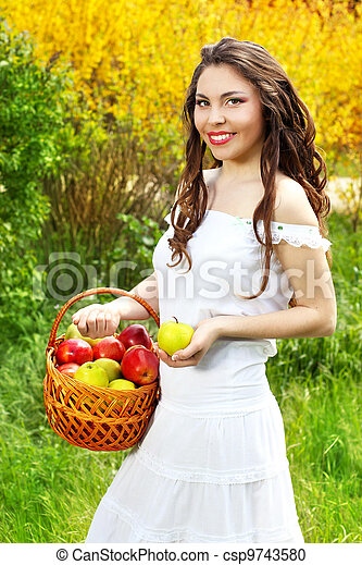 Smiling Female in white dress presents basket of apples