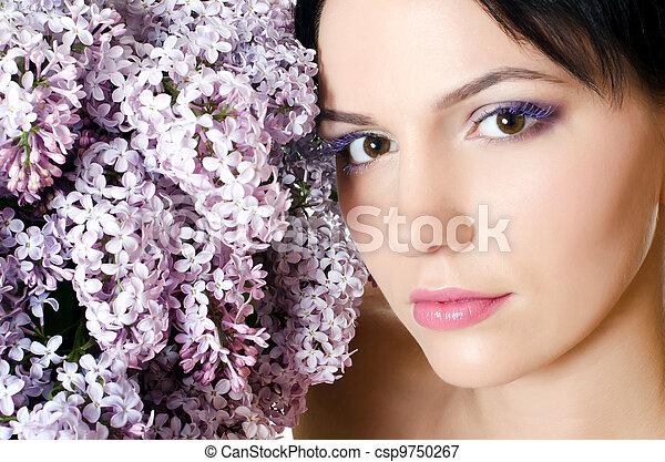 Beautiful woman with spring flowers of a lilac. Skincare - csp9750267