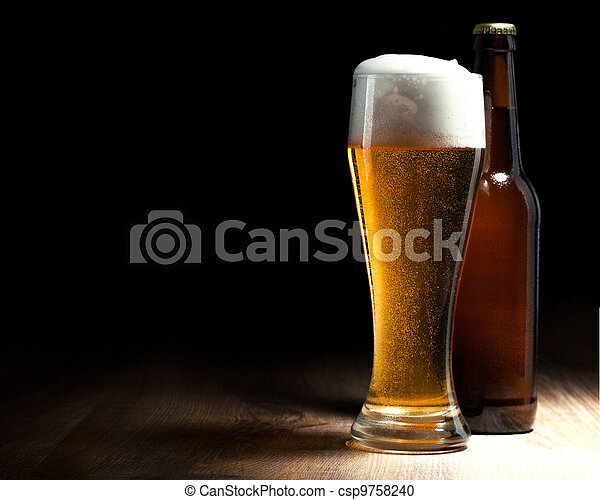 beer glass and bottle on a wooden table - csp9758240