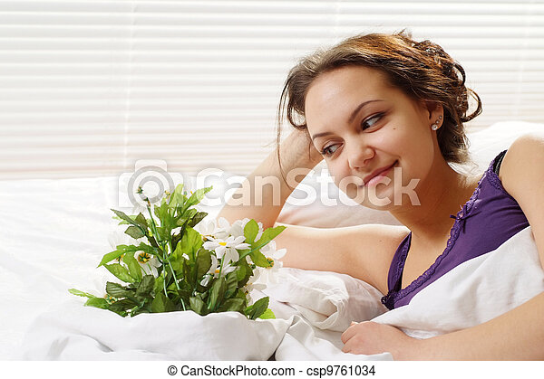 A beautiful caucasian gladness girl in bed with a bouquet of flowers on a light background - csp9761034