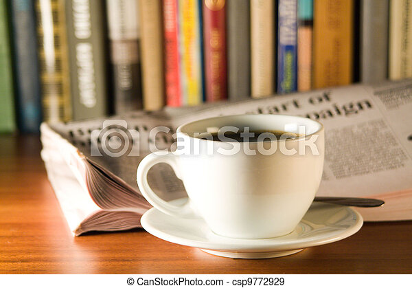 Coffee, newspaper and books on a wooden table. - csp9772929