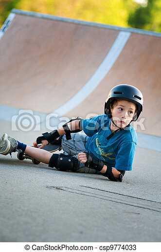 young boy learning to skateboard falls over - csp9774033
