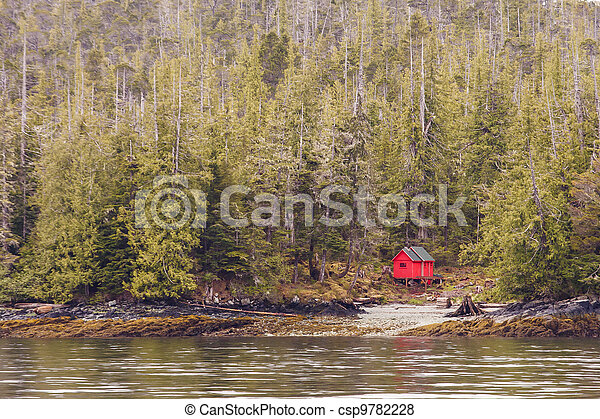 Red Cabin on Edge of Alaskan Waterway in Evergreen Forest - csp9782228