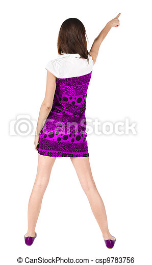 Back view of young brunette woman pointing at wall . - csp9783756