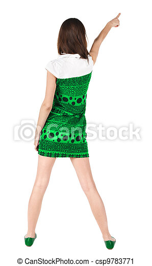 Back view of young brunette woman pointing at wall . - csp9783771