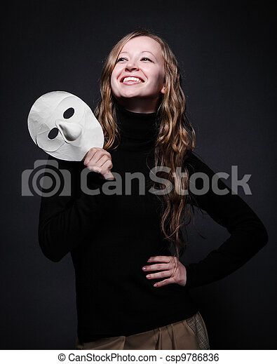 Low key portrait of a beautiful woman holding mask - csp9786836