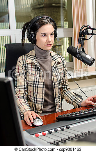 Anchorwoman sitting in front of a microphone on the radio - csp9801463