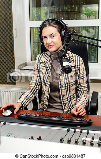 Anchorwoman sitting in front of a microphone on the radio - csp9801487
