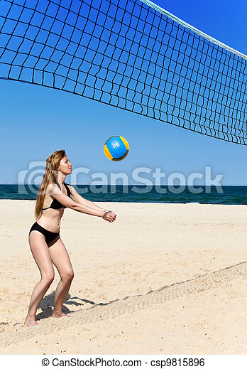 Attractive woman plays in beach volleyball - csp9815896