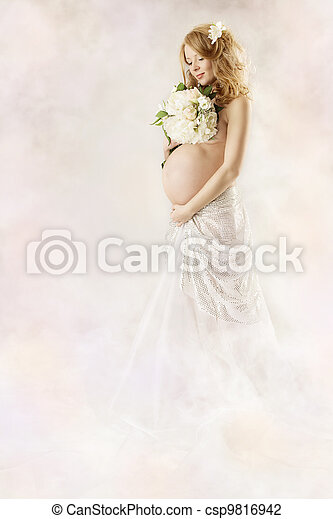 Pregnant woman looking at flowers wearing long white dress. Over abstract art background. - csp9816942