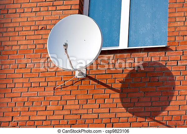 Satellite Dish mounted on  brick wall. - csp9823106