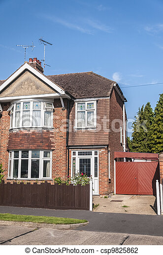 One side of a semi detached house with blue sky - csp9825862