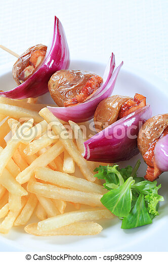 Bacon and potato skewer with fries - csp9829009