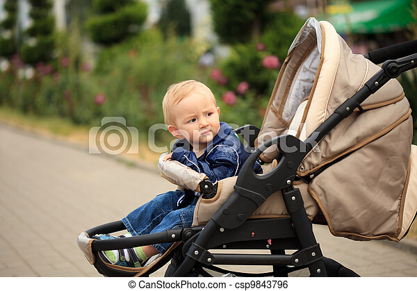 Toddler in baby carriage - csp9843796