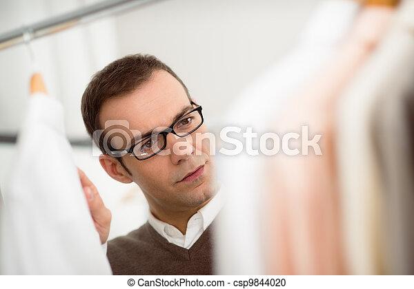 adult man choosing shirt in clothes shop - csp9844020