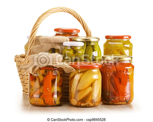 Composition with wicker basket and jars of pickled vegetables. - csp9845528