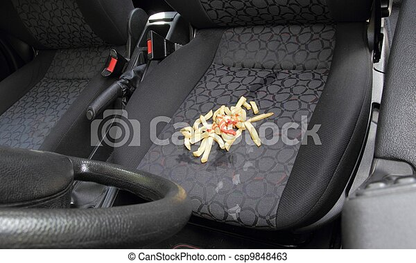 Messy French fries spilt on car seat - csp9848463