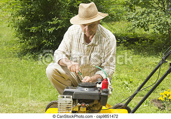 Mid age man repairing lawn mower - csp9851472