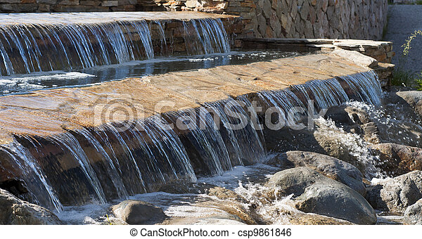 Serene waterfall cascading over rocks into creek - csp9861846