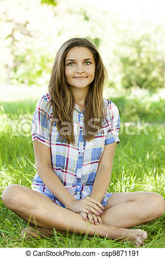 Beautiful teen girl in the park at green grass. - csp9871191