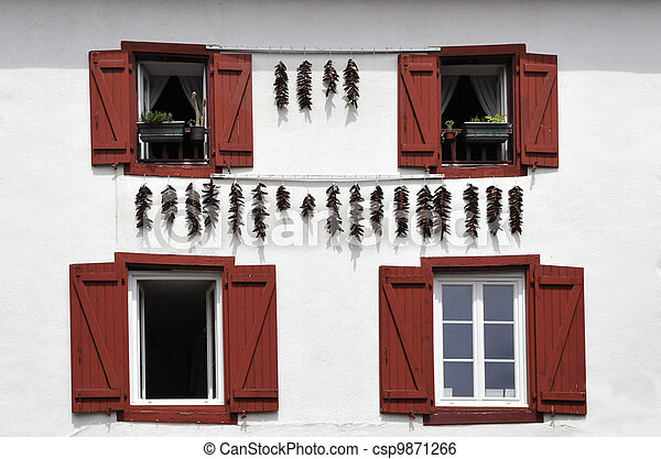 Red Spices hanging on a White Wall with Red Shutters - csp9871266