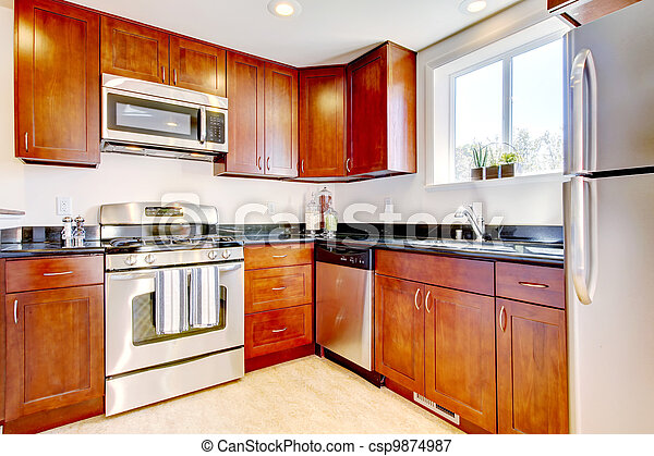 Modern cherry kitchen with steal appliances. - csp9874987