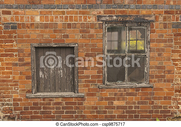 Old decaying wooden window and hatchway with brown paint peeling off - csp9875717