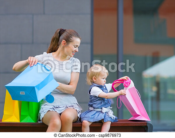 Mother and baby looking into shopping bag - csp9876973