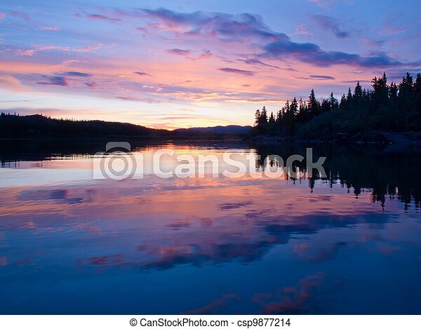 Reflection of sunset sky on calm surface of pond - csp9877214