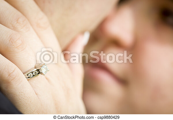 Female Hand with Engagement Ring Touching Fiance's Face - csp9880429