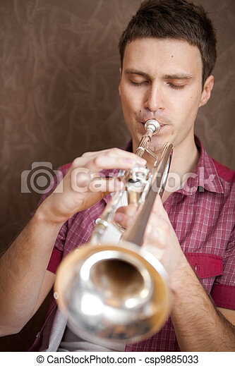 Handsome man playing on a silver trumpet - csp9885033