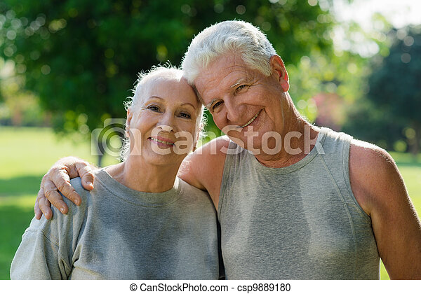 Portrait of elderly couple after fitness in park - csp9889180