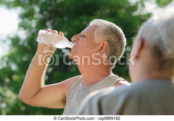 Seniors drinking water after fitness in park - csp9889182