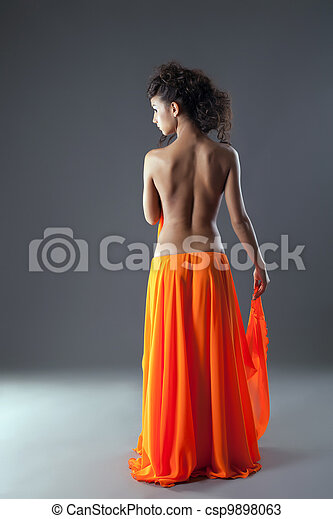 Beautiful young woman in long orange skirt - csp9898063
