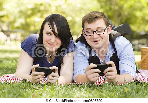 Young Couple at Park Texting Together - csp9898720