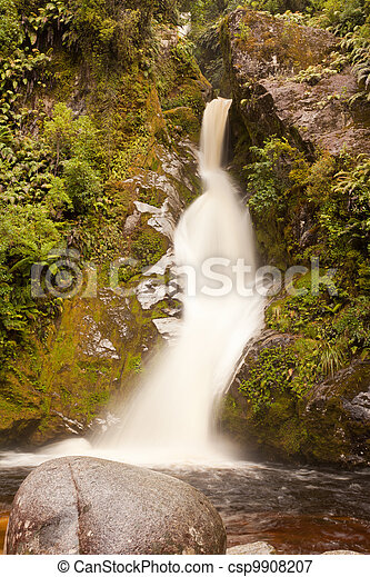 Silky forest waterfall cascading down rocky slope - csp9908207