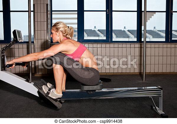 Woman On Indoor Rowing Machine - csp9914438