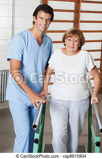 Portrait of a physical therapist assisting senior woman to walk with the support of bars at hospital gym - csp9915904