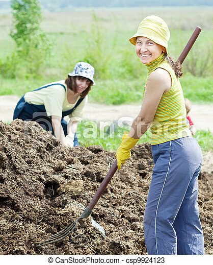 women works with  manure at field - csp9924123