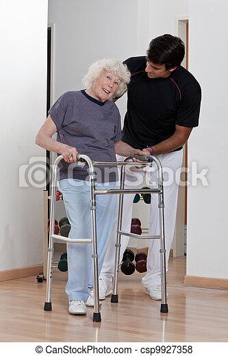 Therapist helping Patient use Walker - csp9927358