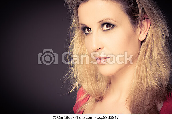 Young adult woman smiling against dark background - csp9933917