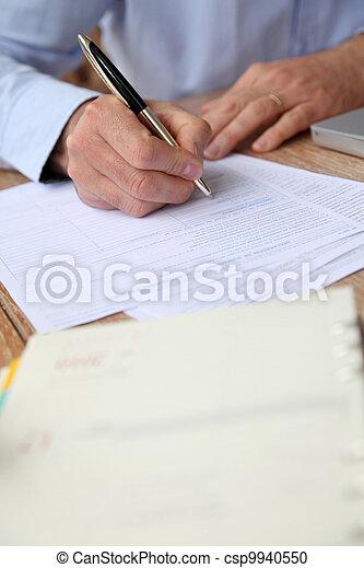 Closeup of senior man filling in tax form