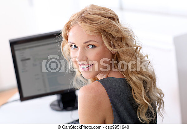Portrait of beautiful woman sitting in front of desktop computer - csp9951940