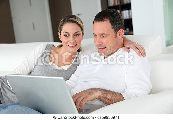 Couple relaxing in sofa with laptop computer - csp9956971