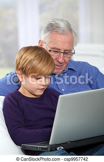 Elderly man with grandkid using laptop computer - csp9957742