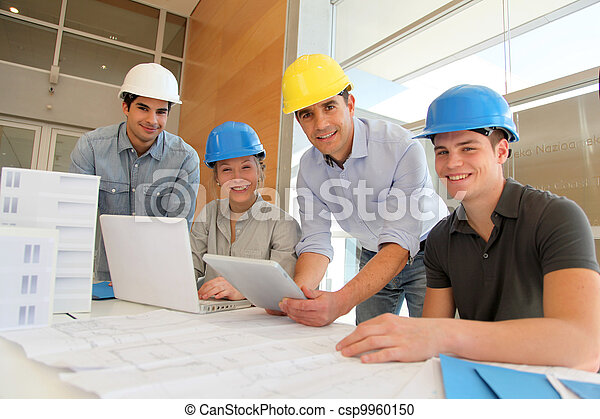 Educator with students in architecture working on electronic tablet - csp9960150