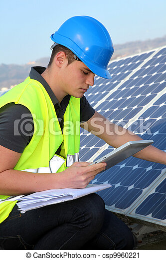 Young adult doing professional training on solar panels plant - csp9960221