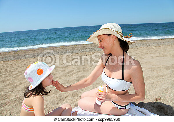 Mother putting sunscreen on her daughter's face - csp9965960