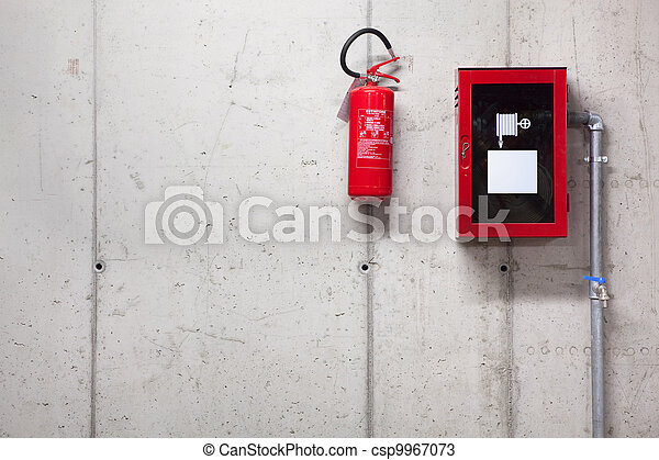 A fire extinguisher and a fire-hose on concrete wall - csp9967073